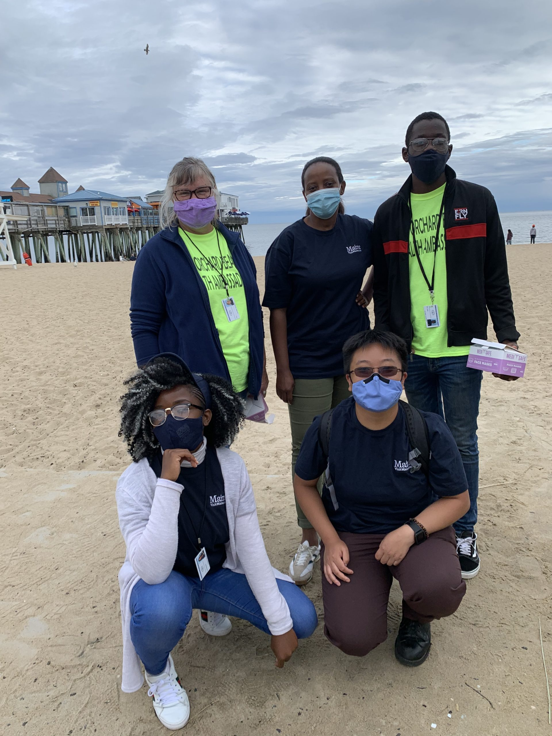 Keep Maine Healthy Ambassadors at Old Orchard Beach this week, masked up and ready to distribute masks and spread the word about COVID-19 safety. (Standing from left) Tracy Taylor, Paulo Paskazia, Beni Lapika; (kneeling from left) Lariska Mali Bengehya and Una Huang.