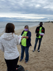 Tracy Taylor and Beni Lapika speak with a beach goer at OOB.